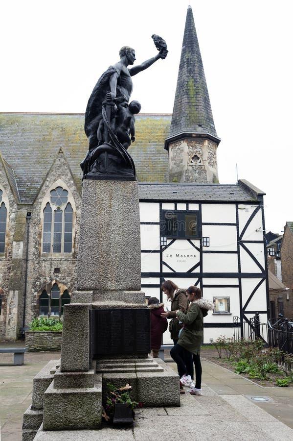 Estatua de bronce de un hombre y de dos niños situados en los jardines del monumento de guerra en el centro de ciudad de Kingston fotografía de archivo