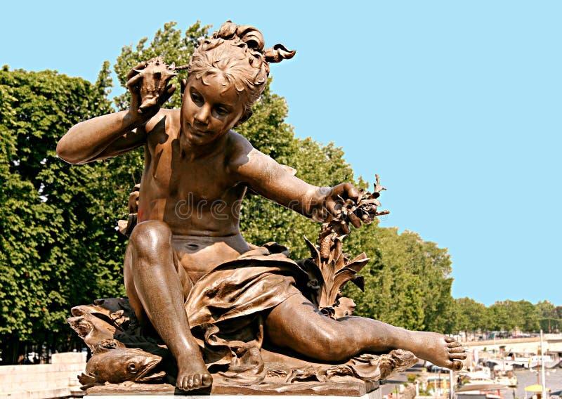 Estatua de bronce de una niña que oye el sonido de una concha y fotografía de archivo libre de regalías