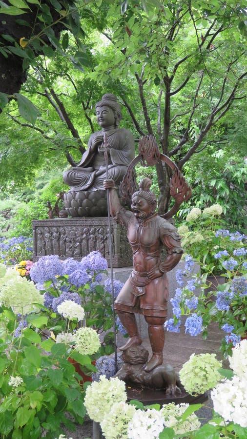 Estatua de Buda con gardian y en el templo de Hasedera en Kamakura fotografía de archivo