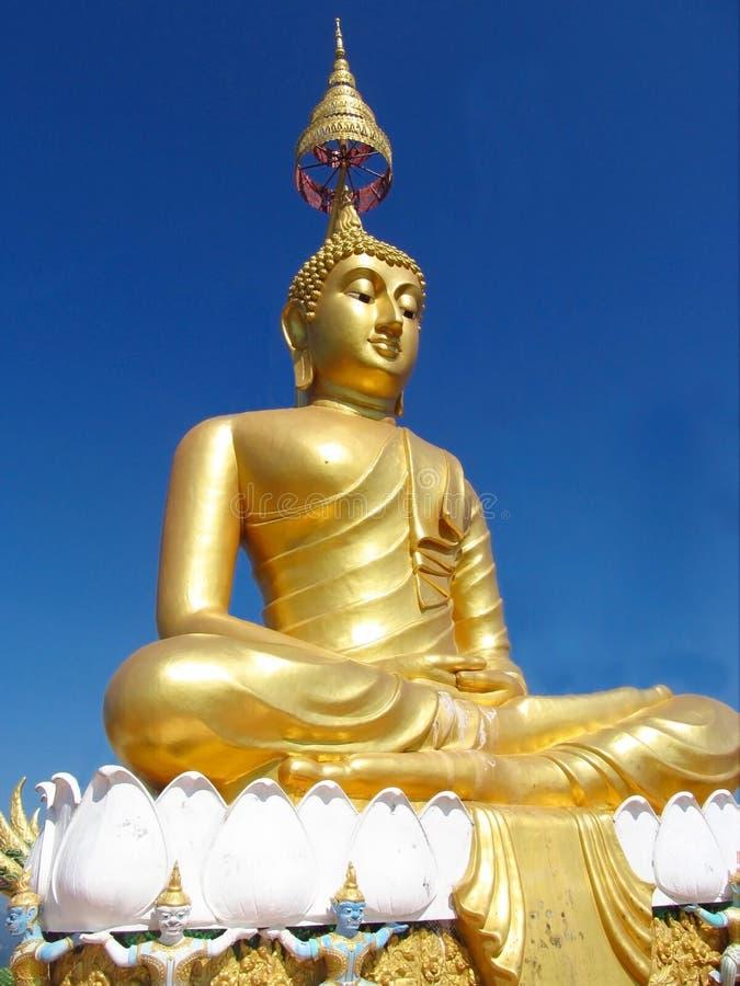 Estatua de Buda del color del oro en templo budista imagenes de archivo
