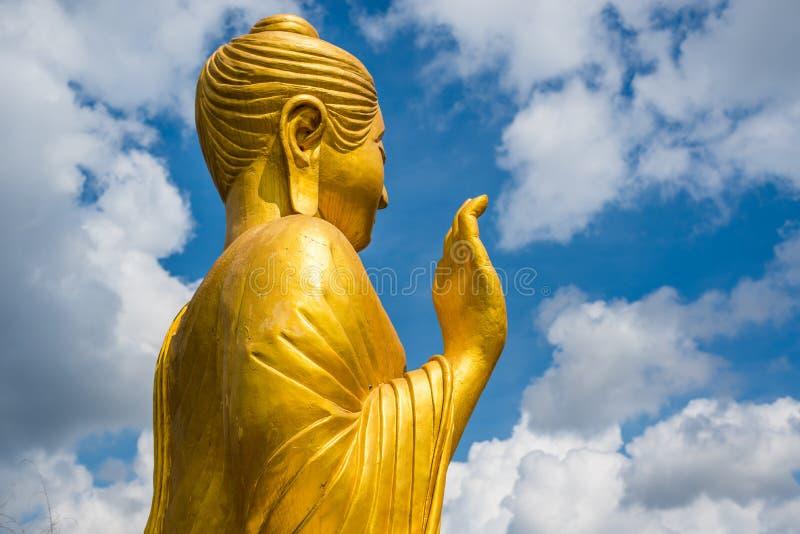 Estatua de Buda del oro en fondo del cielo azul foto de archivo