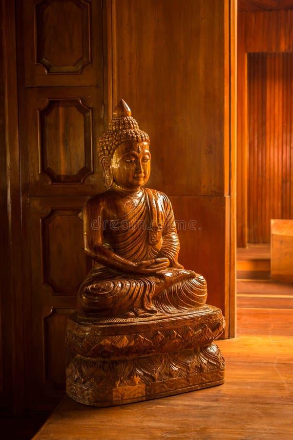 Estatua de Buda hecha de la madera situada en el templo Talla de madera imagen de archivo