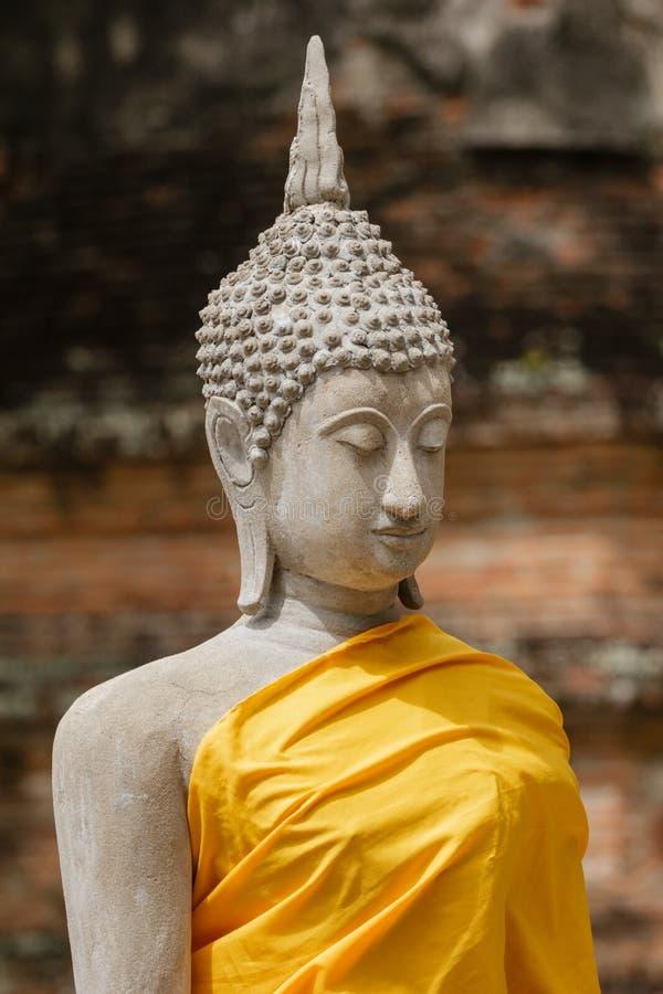 Estatua de Buda que se sienta en retrato amarillo del traje en Ayutthaya fotos de archivo