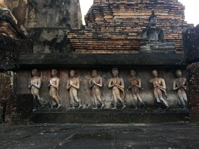Estatua de Buda y escultura antiguas de monjes en una posición derecha y presionar las manos juntas imagen de archivo libre de regalías
