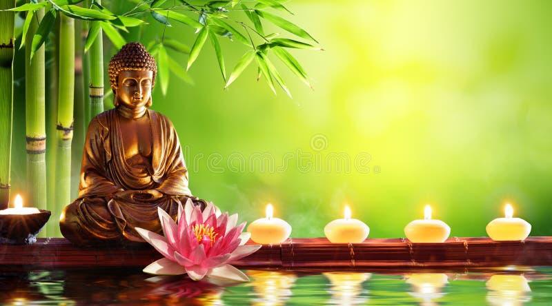 Estatua de Buddha con las velas imagen de archivo libre de regalías