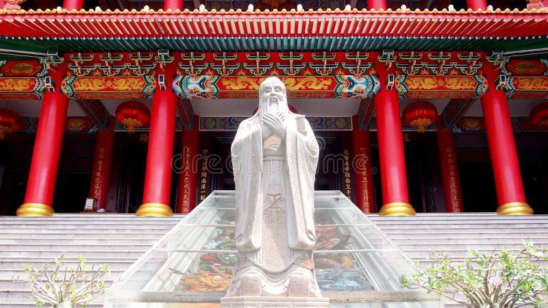 Estatua de Confucio con el fondo tradicional histórico chino de la arquitectura imagenes de archivo