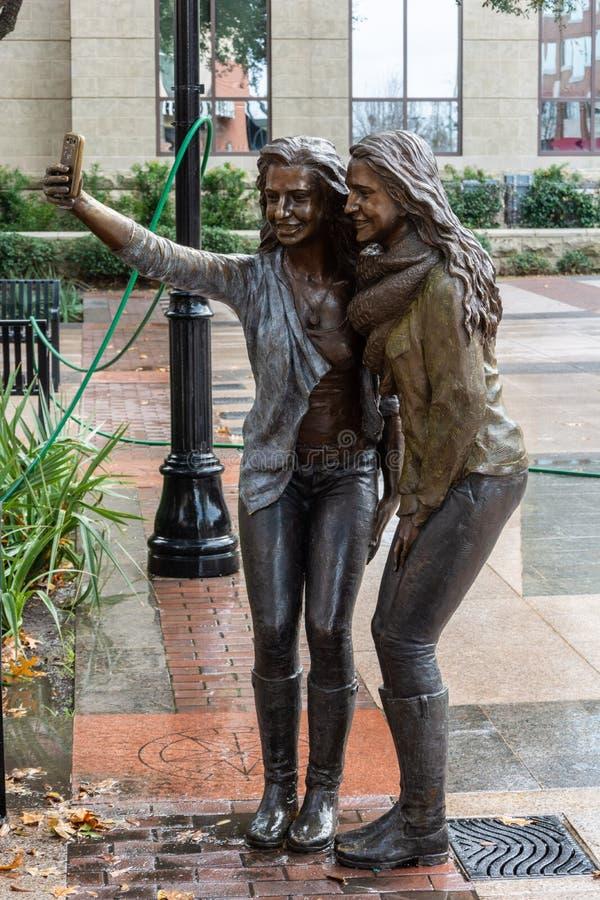 Estatua de dos muchachas que presentan para una foto del selfie en Sugar Land, TX fotos de archivo