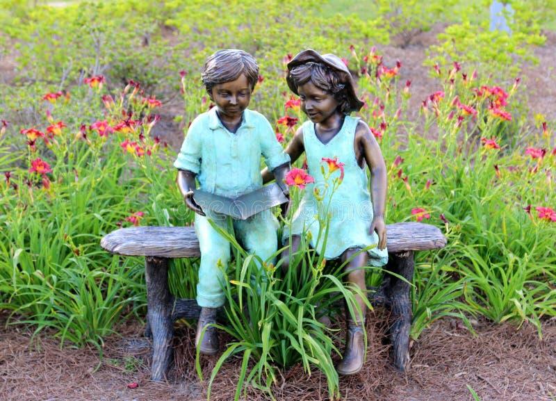 Estatua de dos niños jovenes que leen un libro fotos de archivo libres de regalías
