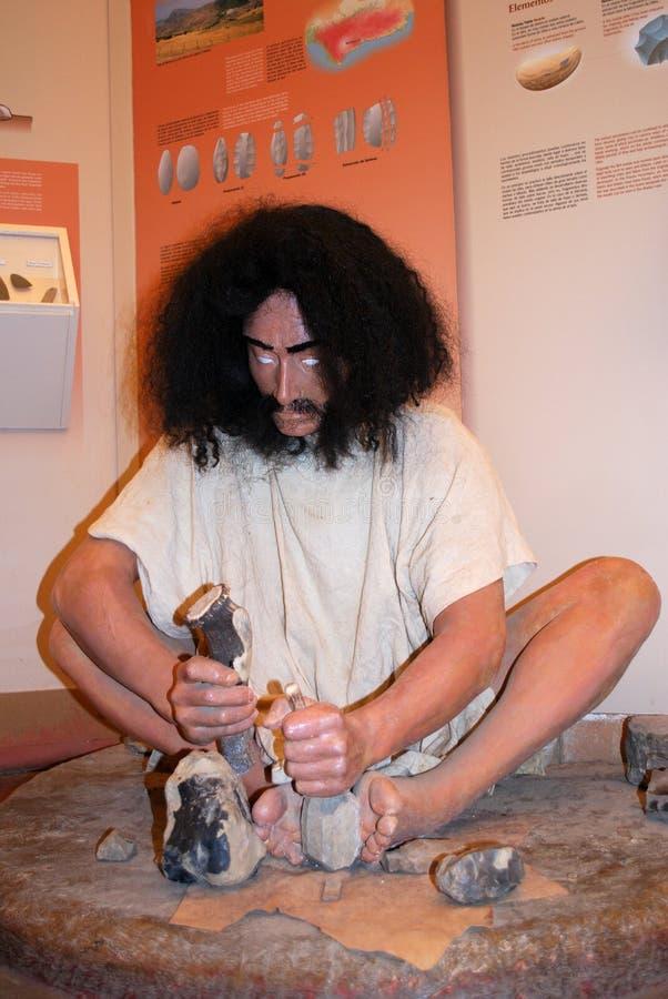 Estatua de la Edad de Piedra de una sentada del hombre que hace las herramientas de piedra, Ronda, España imágenes de archivo libres de regalías