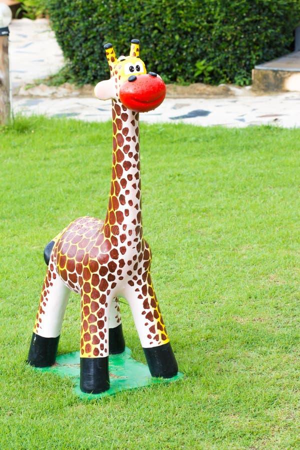 Estatua de la jirafa en el campo verde fotos de archivo
