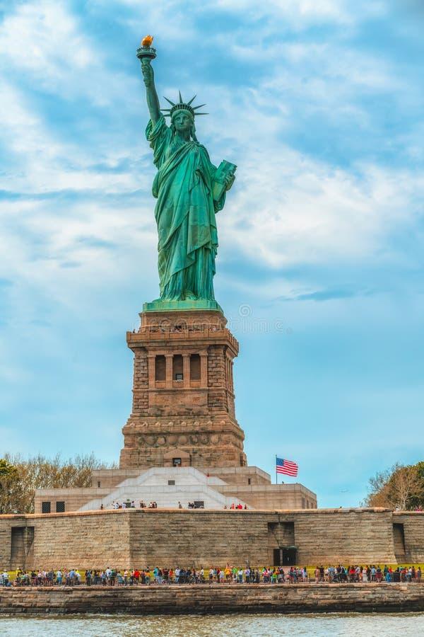 Estatua de la libertad en Liberty Island, New York City Fondo nublado del cielo azul, bandera vertical foto de archivo