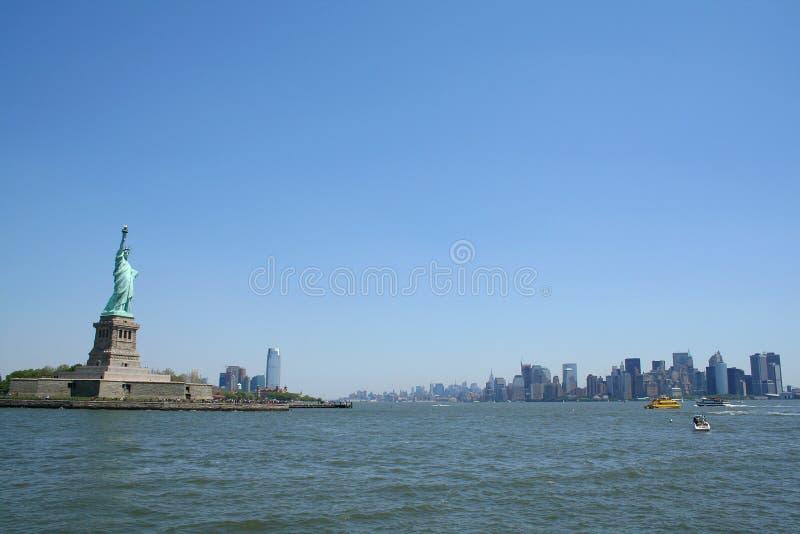 Estatua de la libertad y de Manhattan céntrica imagenes de archivo