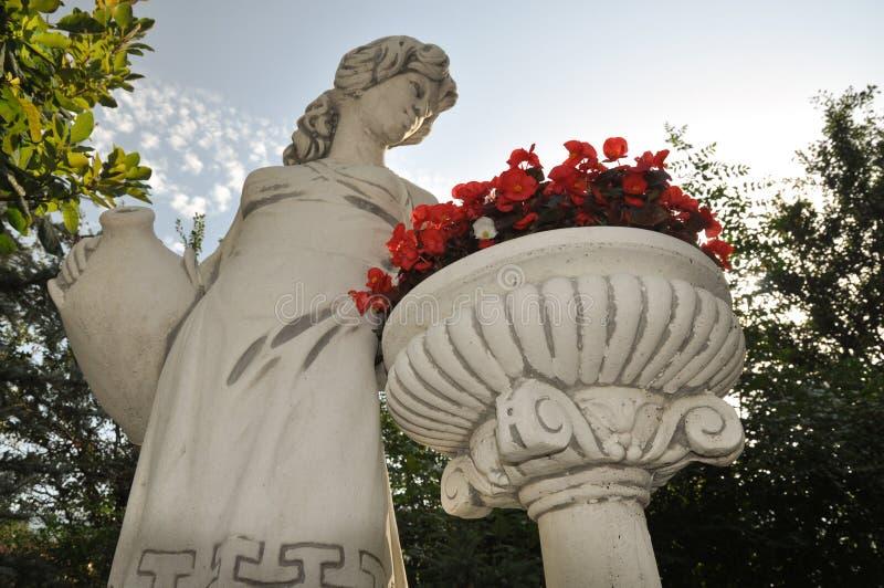 Estatua de la mujer con la cesta de flores foto de archivo