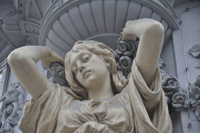 Estatua de la mujer joven en la fachada imágenes de archivo libres de regalías