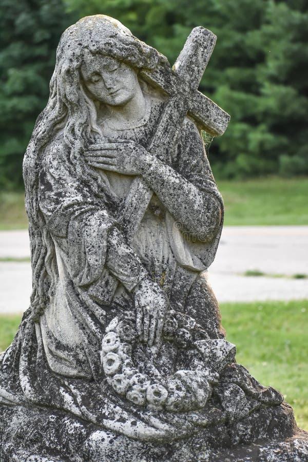 Estatua de la mujer que sostiene una piedra sepulcral de la cruz y de la guirnalda en cementerio fotografía de archivo