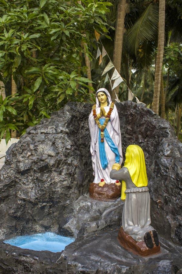 Estatua de la Virgen María en un primer de piedra en un fondo de palmeras verdes fotografía de archivo