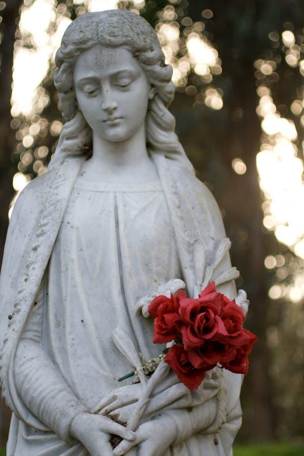 Estatua de mármol que sostiene rosas imagenes de archivo