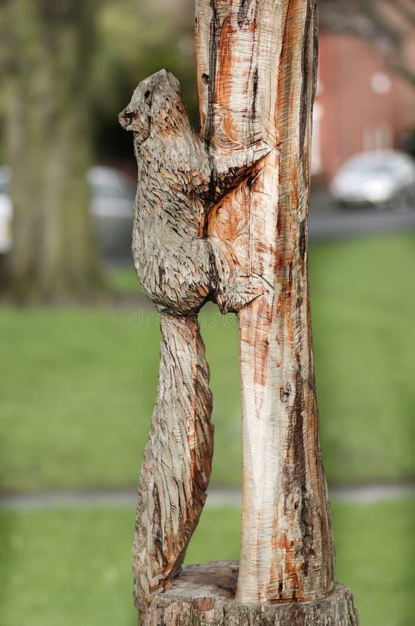 Estatua de madera de la ardilla, decoración del parque en los posts de madera Manch imagenes de archivo