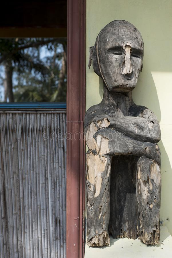 Estatua de madera resistida por una pared amarilla y una puerta abierta con la cerca de bambú imagen de archivo
