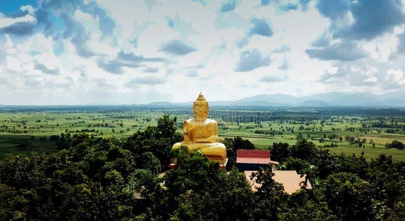 Estatua de oro de Buda en la niebla del pasillo del templo público en f foto de archivo