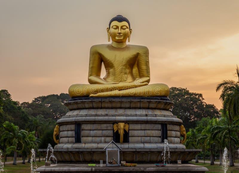 Estatua de oro de Buda en la puesta del sol imagen de archivo libre de regalías