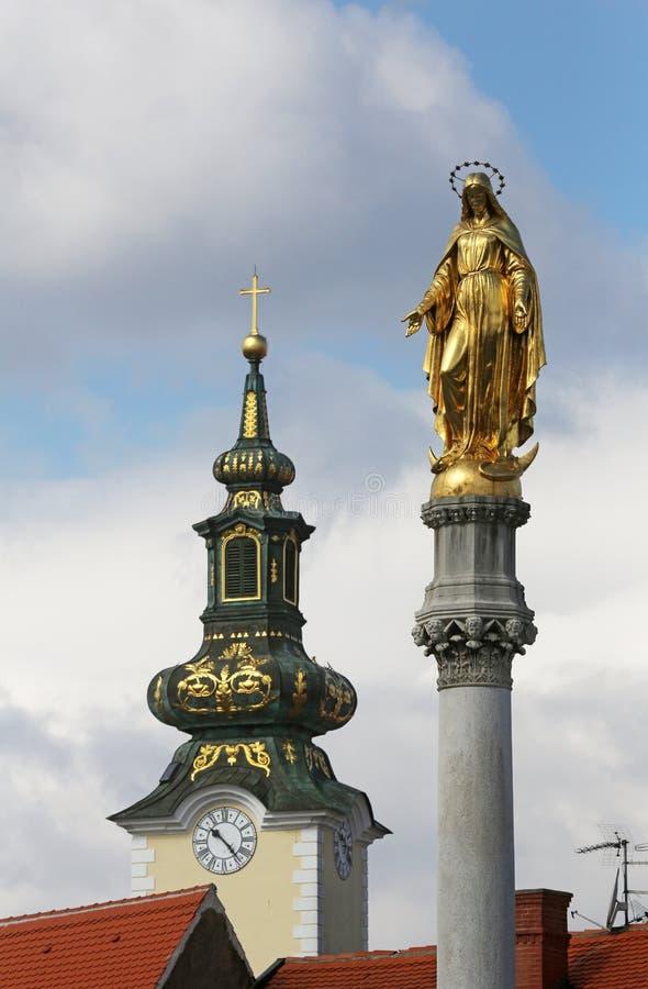 Estatua de oro de la Virgen María e iglesia de St Mary en Zagreb fotografía de archivo