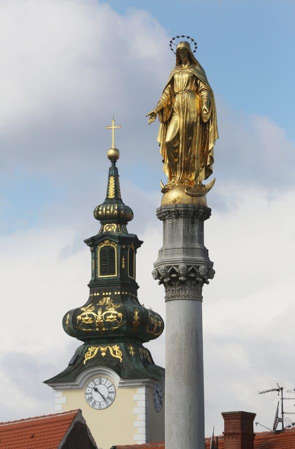 Estatua de oro de la Virgen María e iglesia de St Mary en Zagreb foto de archivo libre de regalías