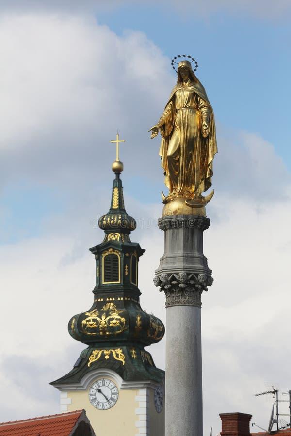 Estatua de oro de la Virgen María e iglesia de St Mary en Zagreb foto de archivo