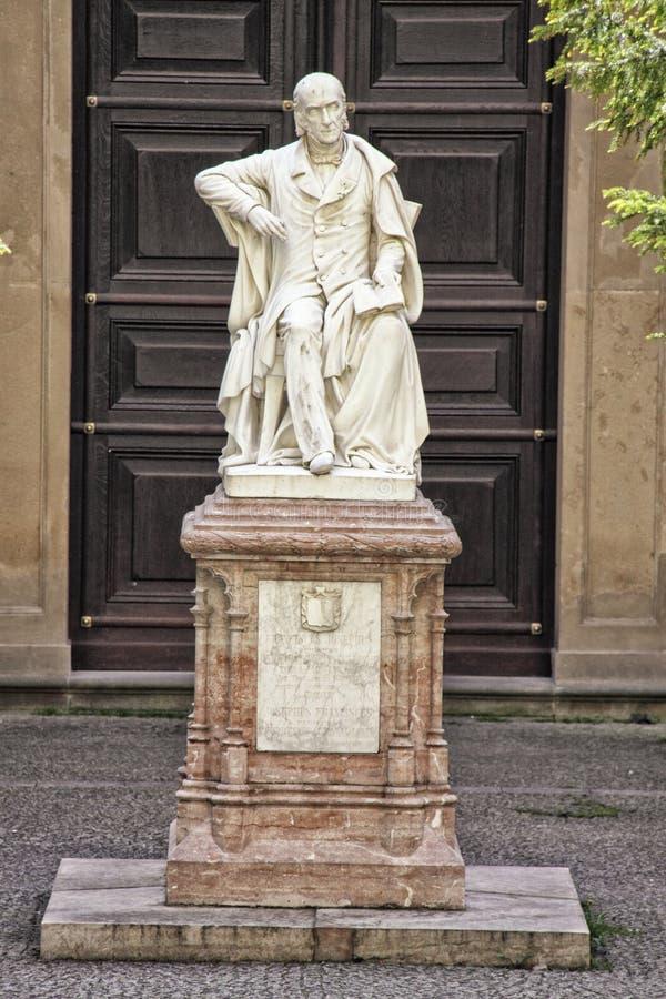 Estatua de piedra de mármol blanca del hombre que se sienta en silla en el pedestal fotos de archivo libres de regalías