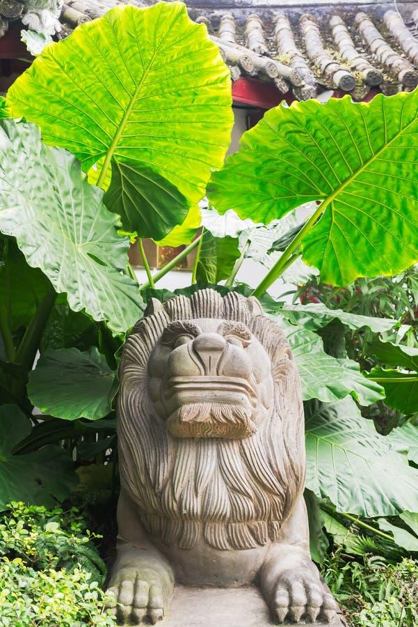 Estatua de piedra del león con las hojas grandes en el fondo imagen de archivo libre de regalías