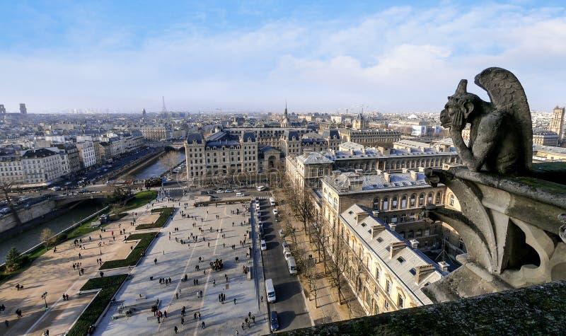 Estatua de piedra famosa de la gárgola en Notre Dame Cathedral With City Of París foto de archivo