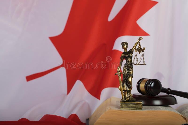 Estatua de Themis y el mazo del juez en un libro Bandera de Canadá adentro imagen de archivo