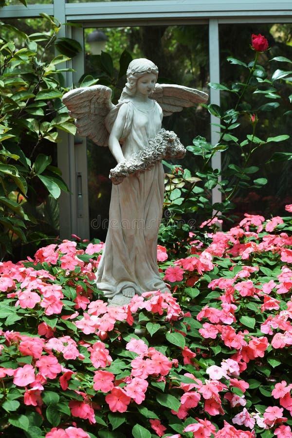 Estatua de un ángel en flores foto de archivo libre de regalías