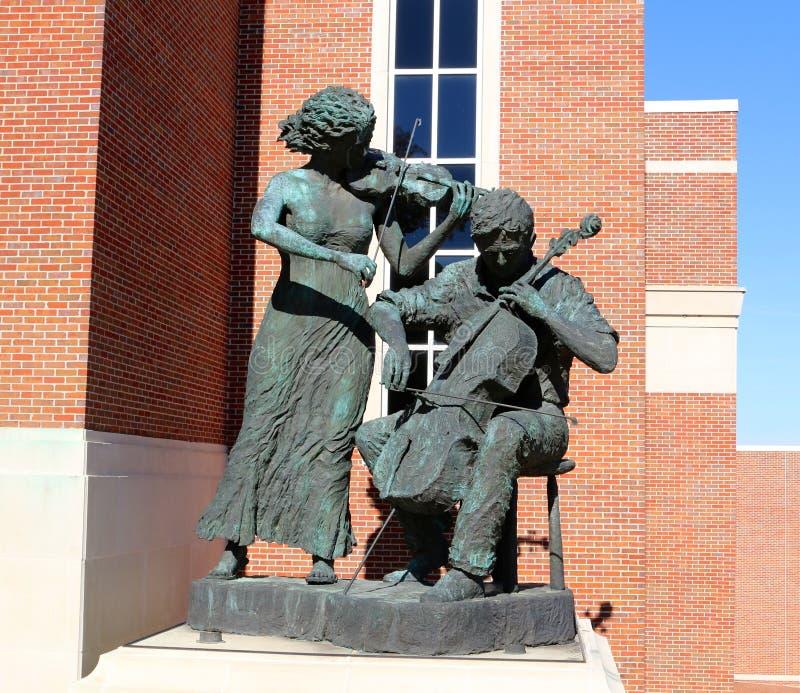 Estatua de un hombre y de una mujer que tocan los violines en Gertrude Castellow Ford Center en el campus de Ole Miss fotos de archivo libres de regalías