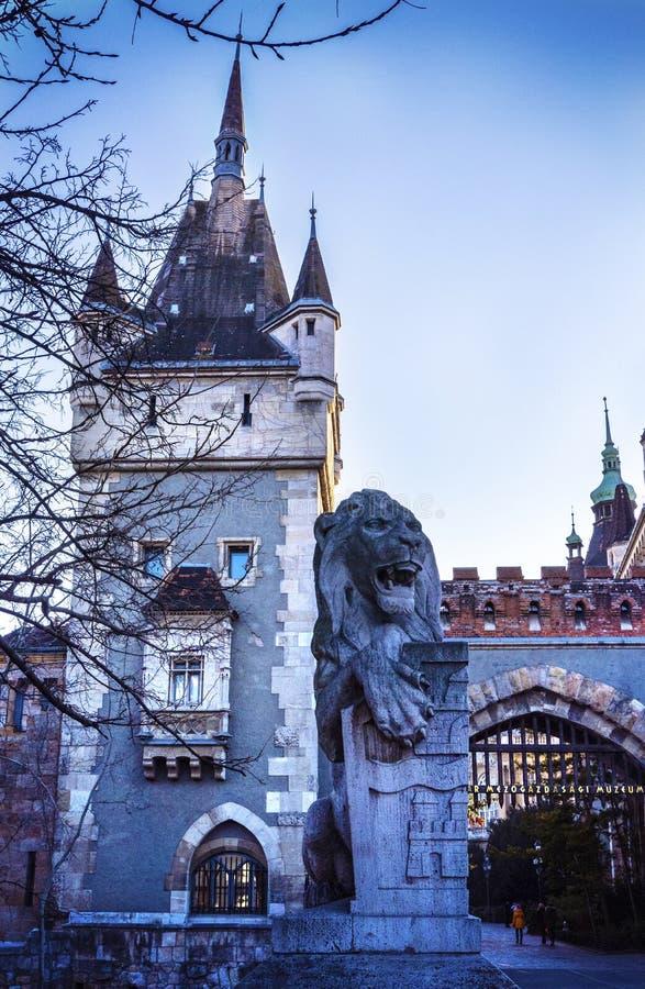 Estatua de un león en la entrada y la puerta de piedra en la entrada al castillo de Vajdahunyad en el parque de la ciudad de Buda fotografía de archivo libre de regalías