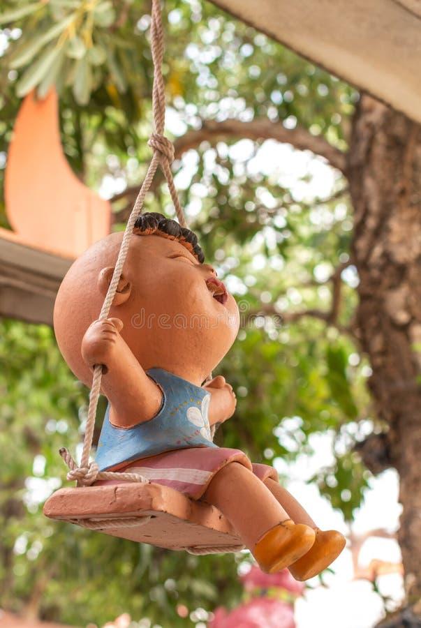 Estatua de un niño que se sienta en un oscilación que sonríe feliz fotografía de archivo