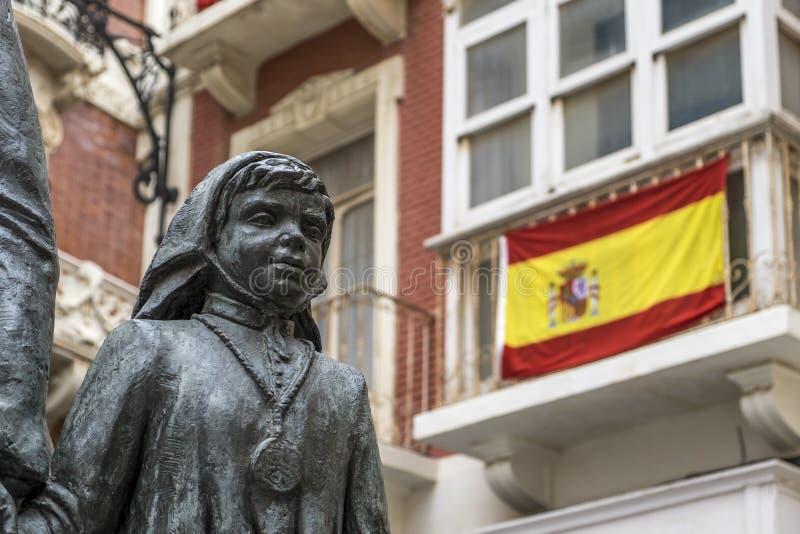 Estatua de un niño y de la bandera española fotografía de archivo libre de regalías