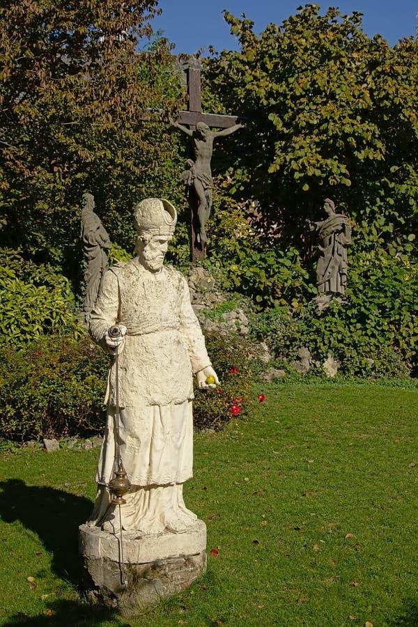 Estatua de un sacerdote delante de Jesús en la cruz con Maria y Mary Magadelen que se arrodillan al lado de ella foto de archivo