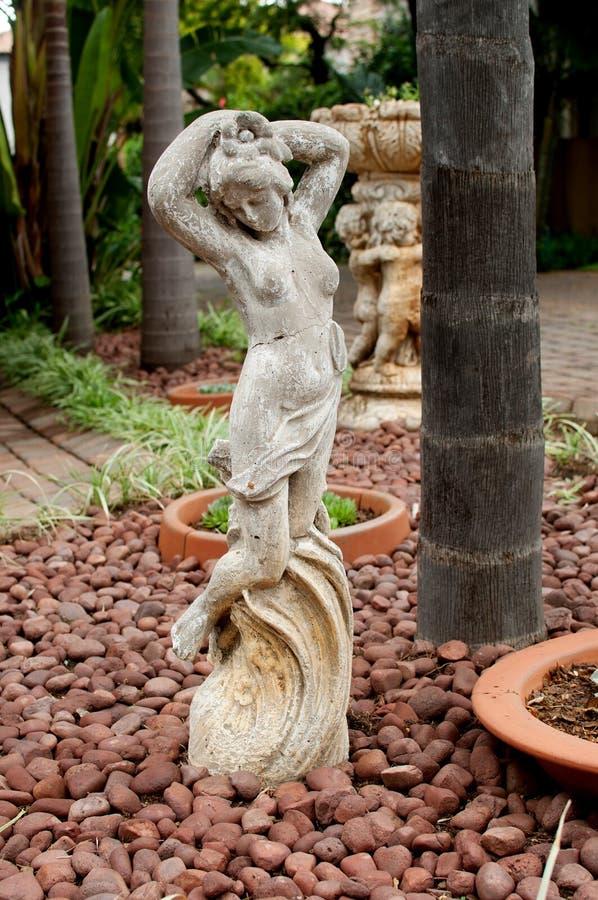 Estatua de una muchacha hermosa en jardín de piedras imágenes de archivo libres de regalías