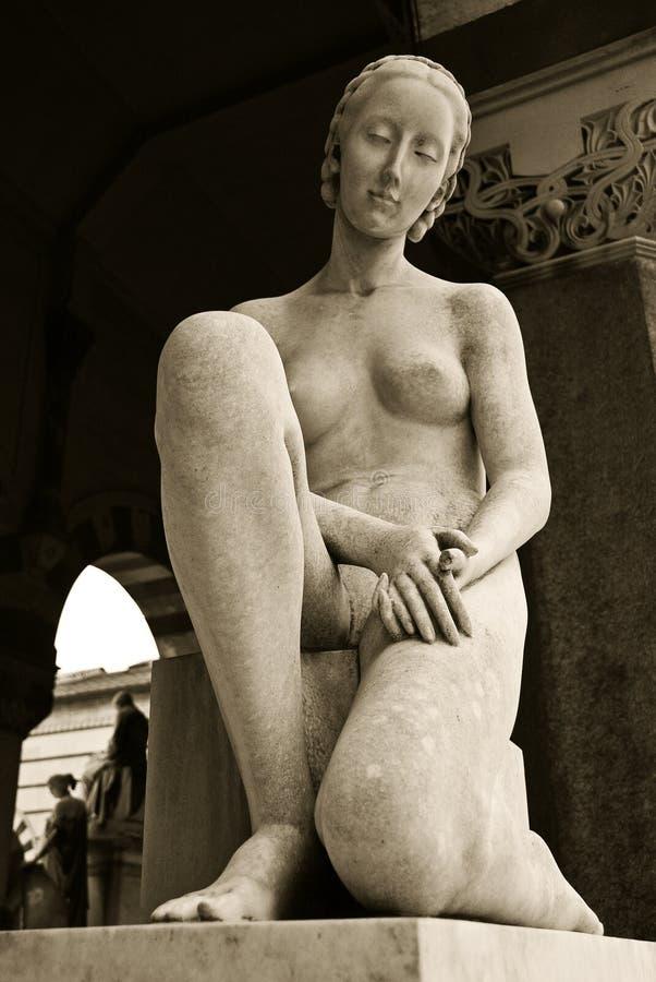 Estatua de una mujer que se sienta fotos de archivo