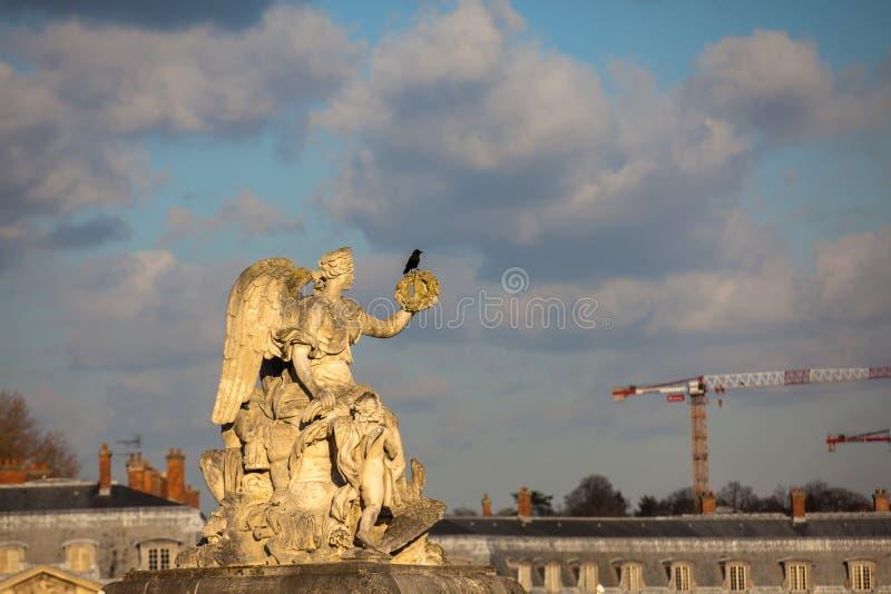 Estatua del ángel en la entrada del palacio de Versalles en un día de invierno de congelación momentos antes de la primavera imagenes de archivo