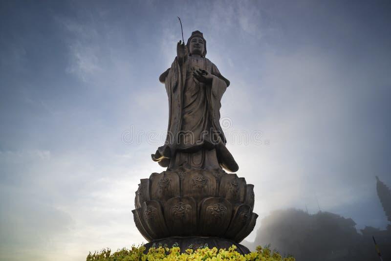 Estatua del Bodhisattva en pico de monta?a de Fansipan la monta?a m?s alta del cielo azul y de la nube de la hermosa vista del co fotos de archivo