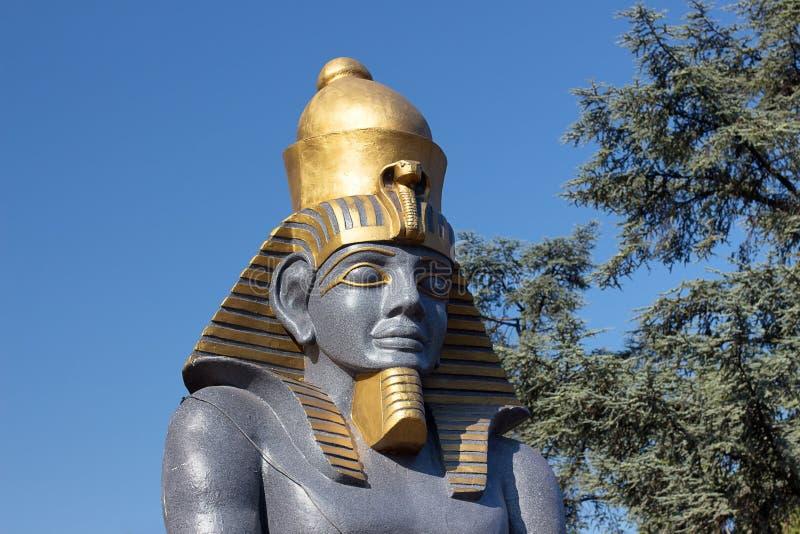 Estatua del faraón contra un fondo del cielo azul y de árboles Esculturas decorativas con motivos egipcios foto de archivo