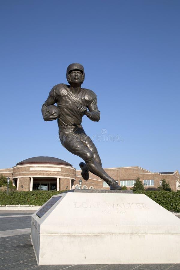 Estatua del futbolista famoso delante del edificio de la universidad fotos de archivo