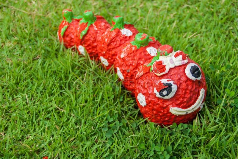 Estatua del gusano rojo de la sonrisa en la hierba foto de archivo libre de regalías