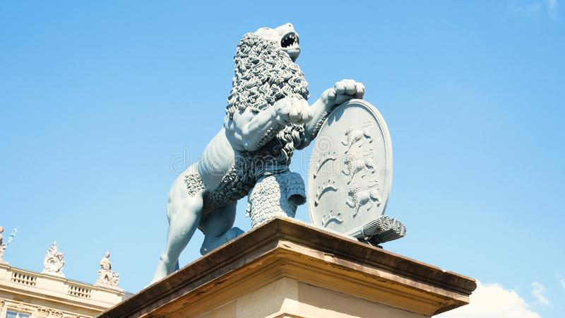 Estatua del león, Neues Schloss detrás de la fuente, domicilio del Ministerio de Finanzas, palacio en el cuadrado de Schlossplatz fotografía de archivo libre de regalías