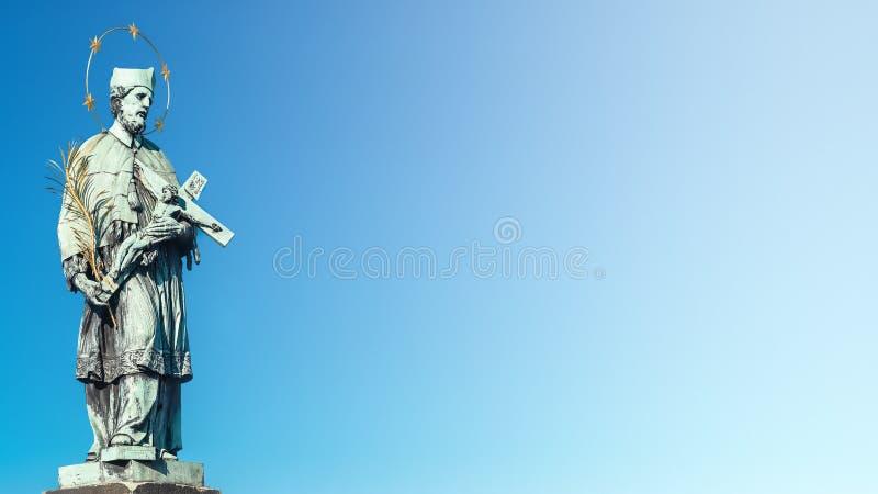 Estatua del santo con la cruz en Charles Bridge en Praga en el cielo azul de la pendiente, República Checa, tiempo de verano imagen de archivo libre de regalías