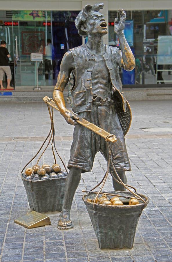 Estatua del vendedor de calle con dos cestas en Kunming fotografía de archivo