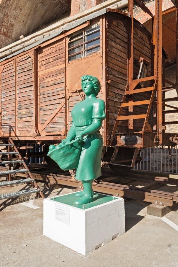 Estatua delante de un carro viejo del ferrocarril en Cerbere, Francia foto de archivo