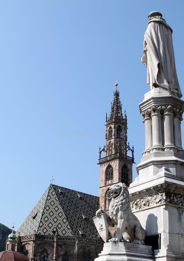 Estatua e iglesia de parroquia gótica en Bolzano, Italia fotografía de archivo
